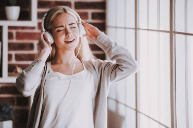 Young Smiling Woman Listening Music in Headphones. Beautiful Blonde Woman in Casual outfit and closed eyes Standing next to Window and Enjoing Listening Music in Headphones at Home.