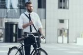 Fiatal, jóképű üzletember lovaglás kerékpár a munka. Eco-barátságos és az egészséges és aktív életmód. Üzletember, lovaglás kerékpár munka a városi utcán. Üzleti koncepció. Életmód fogalom.
