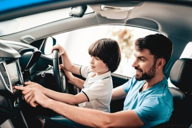Man With Kid Are Sitting At The Wheel Of New Vehicle. Smiling Family. Car Buying In A Showroom. Automobile Salon. Cheerful Driver. Happy Together. Father And Son. Good Mood. Great Trade.