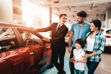 Happy Young Family Are Choosing A New Car In Showroom. Dialogue With Dealer. Cheerful Customer. Auto Rewiew. Make A Decision. End Of A Deal. Good Offer. Buyer And Seller. Business Trade.