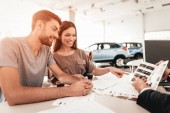 Happy Young Family Are Choosing A New Car In Showroom. Dialogue With Dealer. Cheerful Customer. Automobile Salon. Make A Decision. Cup Of Coffee. End Of A Deal. Good Offer. Buyer And Seller.