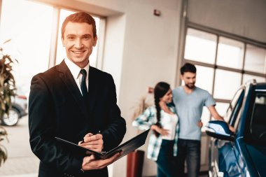 Car Dealer Camera Posing With A Buyer On Background. Cheerful Customer. Automobile Salon. Make A Decision. End Of A Deal. Good Offer. New Buying. Business Trade. Confident Seller. Purchase Order.