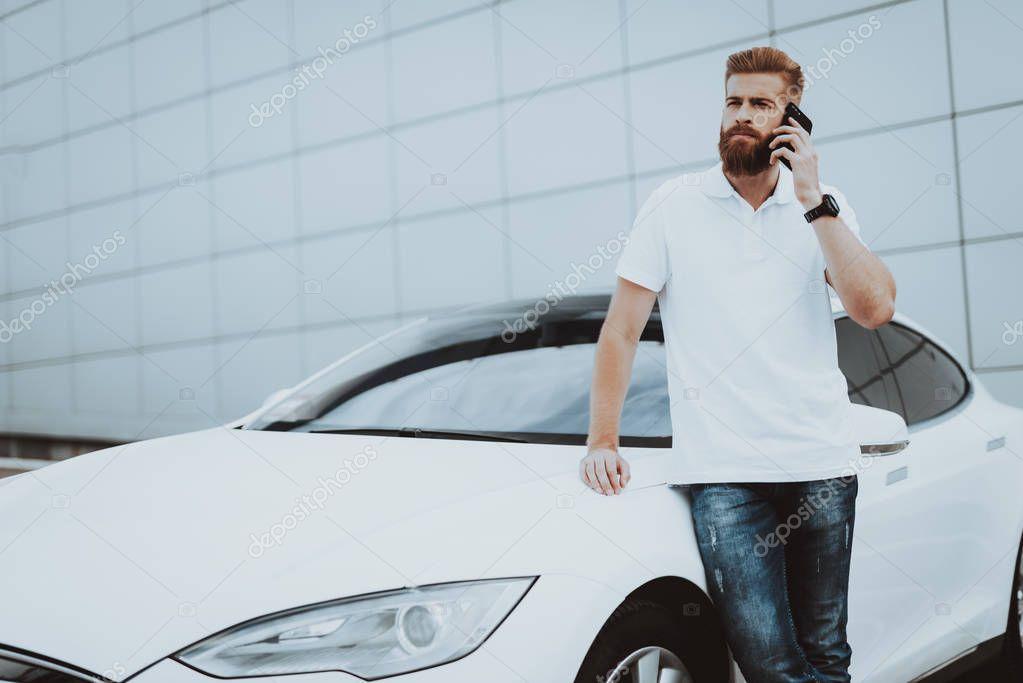 Man Talks On Phone Near Tesla Car. Charge Station. Automobile Parking Lot. Innovation Technology. New Generation Electro Hybrid Vehicle. Ecology Station. Futuristic Power. Gadget Concept.