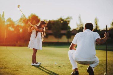 Happy Young Family Relax on Golf Field in Summer. Relaxing in Golf Club. Sports in Summer. Outdoor Fun in Summer. Family Fun Concept. Healthy Lifestyle Concept. Little Girl. Green Grass.