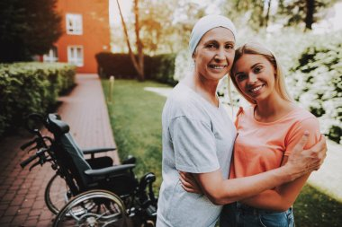 Patient Undergoes Rehabilitation. Cancer Patient Stands Up . Woman with Daughter. Woman Glad See Daughter. Recovering Woman. Remission. Cancer Patient. Embrace. Woman Nearby Wheelchair. Smiling Women.