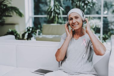 Patient Undergoes Rehabilitation. Cancer Patient on Sofa. Recovering Woman. Remission. Clinic. Cancer Patient. Flowerpots with Flowers. Pink Ribbon. Breast Cancer. Music on Tablet. White Headphones.