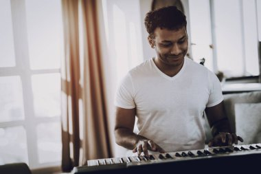 Afro American Young Man Is Playing Synthesizer At Home. Happy Songwriter. Morning Leisure. Digital Format Sound Record. Working Musician. Musical Hobby. Hands On Keyboard. Cheerful Professional.