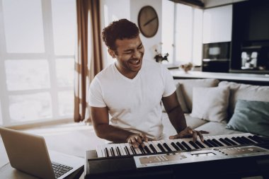 Afro American Young Man Is Playing Synthesizer At Home And Sing. Happy Songwriter. Morning Leisure. Digital Format Sound Record. Working Musician. Musical Hobby. Hands On Keyboard.