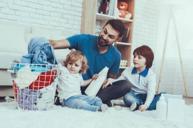 Leisure Time. Man. Smile. Two Boys. Help Wash Clothes. Father. Baby with Bright Hair. Smiling Kids. Spends Time. Happy Together.Home Time. Family. Holidays. Father Two Boys. Dirty Laundry. Basket.
