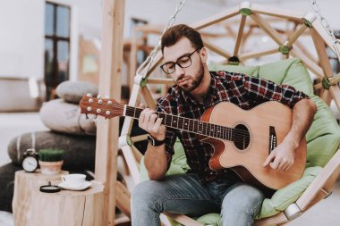Guitar. Coffee. Create Ideas. Inspiration. Creative Worker. Hanging Chair. Sit. Brainstorm. Young Guy. Businessman. Working in Office. Businesspeople. Workplace. Relaxation. Comfortable.