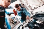 Fotografie Junge Auto mechanische Reparaturen Auto mit einem Schraubenschlüssel. Unter der Haube. Professionelle Uniform. Laptop verwenden. Engineering-Spezialisten-Team. Service-Station-Konzept. Kfz Diagnose. Arbeiten In Garage