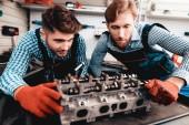Dvě automechanici kontrolují Detail v garáži. Profesní uniformy. Jistý inženýrství odborný pohled. Ochranné rukavice. Práce v garáži. Mladý opravář představuje koncept.