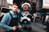 Mladí Auto mechanik oprav automobilové Hub v garáži. Profesní uniformy. Čerpací stanice koncept. Jistý inženýr pohled. Podrobnosti opravy. Pod vozidlem. Automobilová Diagnostika.