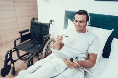 Man Watch Video in Pad in Headphones and Hold Cup. Portrait of Happy Handsome Invalid Lies in White Bed Near Modern Black Wheelchair and Looks at Tablet Screen and Drinks Coffee or Tea