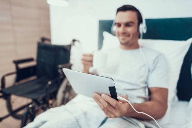 Man Watch Video in Pad in Headphones and Hold Cup. Blurred Portrait of Happy Handsome Invalid Lies in White Bed Near Modern Black Wheelchair and Looks at Tablet Screen and Drinks Coffee or Tea