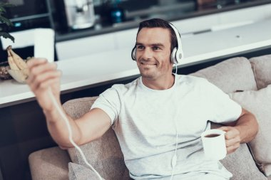 Man Makes Selfie in Headphones while Drinking Tea. Portrait of Smiling Handsome Brown Haired Young Man Wearing Casual Clothes Sitting on Sofa and Looking at Smartphones Screen