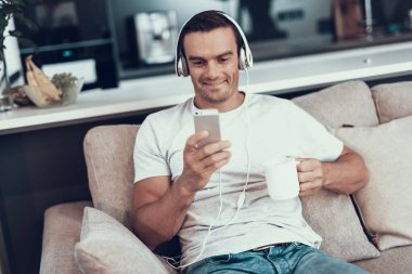 Man Listens to Music in Earphones and Drinks Tea. Portrait of Smiling Handsome Young Man Sitting on Sofa Looking at Smartphones Screen Using Headphones. Male Holds Cup of Coffee in Hands.