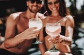 Fotografie Lächelnde paar tranken Cocktails am Pool. Schöne junge Paar Gläser mit alkoholischen Getränken halten und Spaß am Pool. Happy Friends Enoying Poolparty. Sommerurlaub-Konzept