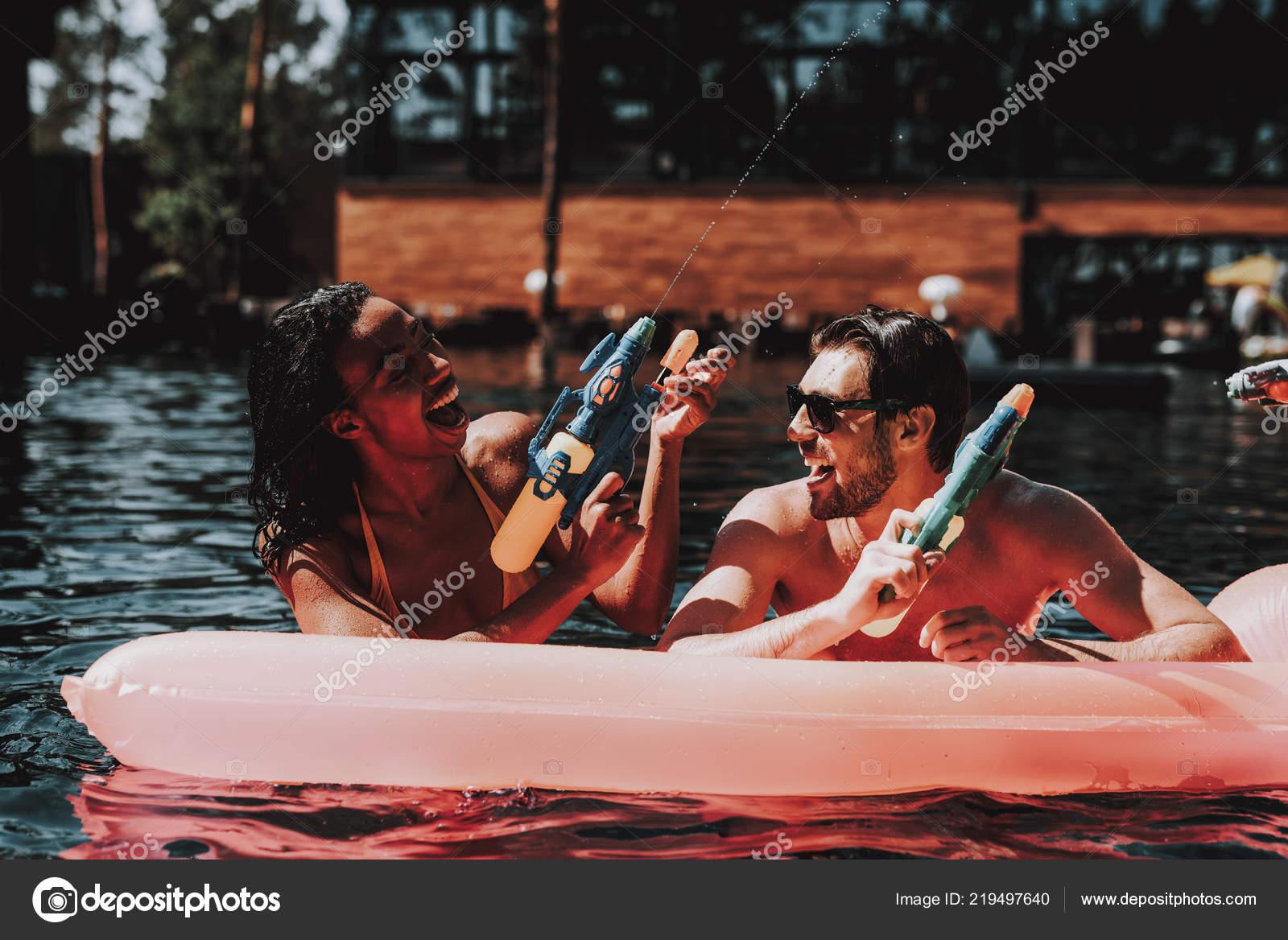 5e1ad47f22356 Joven sonriente pareja divirtiéndose en la piscina. Joven feliz gente  jugando juntos con pistolas de agua colorida en la piscina al aire libre.  Amigos de ...