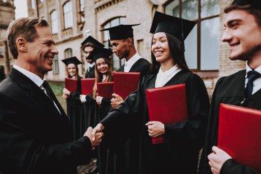 Cheerful. Teacher. Handshake. Students Diplomas. Courtyard. University. Finish Studies. Graduate. Guys. Greet. Group of Young People. Good Mood. Have Fun. Friendship. Knowledge. Cap. Celebration.