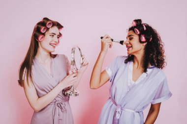 Two Girls with Hair Curlers. Pink Background. Mirror and Brush. Celebrating Women's Day. March 8. Smiling Girl with Mirror. Surprised Woman. Happy Woman. Happy Emotions. Girls with Hair Curlers.