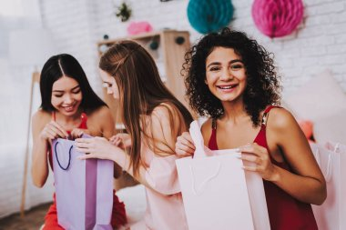 Celebrating Women's Day. Red Dress. Pink Background. Emotional Women. Happy Woman. Gift Bag. Girls Look in Bag. Beautiful Girl. Womans Emotion. Woman Open Gifts. March 8. White Interior. Color Packs.