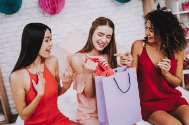 Celebrating Women's Day. Red Dress. Pink Background. Emotional Women. Happy Woman. Gift Bag. Girls Look in Gift Bag. Beautiful Woman. Womans Emotion. Girls Open Gift Puck. White Interior. Color Packs.