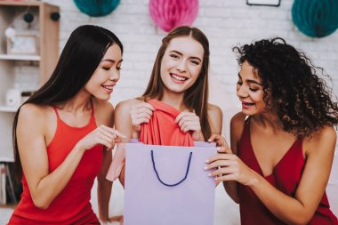 Celebrating Women's Day. Red Dress. White Background. Emotional Women. Happy Woman. Gife Bag. Girls Look in Gift Bag. White Interior. Color Packs. Beautiful Girl. Womans Emotion. Woman Open Gift Puck.