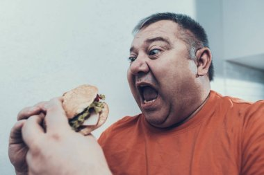 Hungry Fat Mat in Oranfe T-shirt with Burger. Man with Bulimia. Unhealthy Lifestyle Concept. Man with Overweight. Unhealthy Food. Open Mouth. Exited Man. Diet and Healthcare Concept.