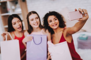 Red Dress. Make Selfies. Celebrating Women's Day. Emotional Women. Happy Woman. Gife Bag. Smiling Girls Look in Phone. Beautiful Girl. Womans Emotion. Three Color Bag. White Interior. Color Packs.