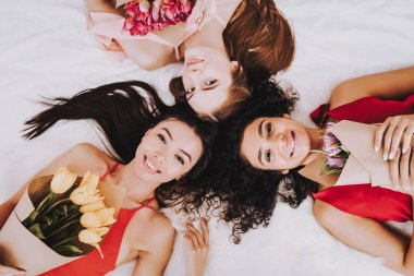 Happy Girls with Flowers. Celebrating Women's Day. Emotional Women. Cheerful Women. Beautiful Girl. Women Lying on Bed with Flowers. International Women with Gifts. Bouquets Flowers on March 8.