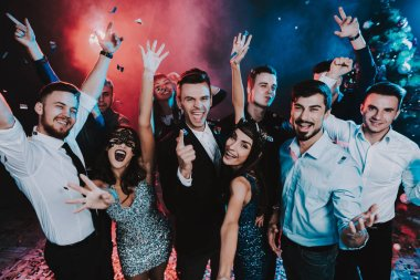 Smiling People Celebrating New Year on Party. Happy New Year. People Have Fun. Indoor Party. Celebrating of New Year. Young Woman in Dress. Young Man in Suit. Exited People. Hands Up.