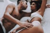 Junge schöne Paar in Unterwäsche auf dem Bett liegend. Gut aussehender Mann und attraktive Frau verliebt. Leidenschaftliche romantische Paare Sex zu Hause haben. Leidenschaft, intime Beziehung und Liebe Konzept