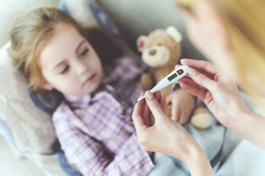 Careful Mom Sits Near Child and Holds Thermometer. Attentive Mother Sits Near Sick Little Daughter Checking Kids Temperature. Pretty Ill Girl has Cold and Fever Lying on Sofa under Blanket or Plaid