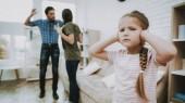 Fotografia Bambino si chiude le orecchie. Bambino e genitori litiganti. Problemi familiari. I genitori lo scandalo. Bambino spaventato. Persona arrabbiata. Relazione complicata. Litigio della famiglia. Cattivi genitori. Bambini di sofferenze. Bambino infelice
