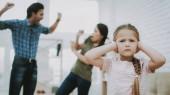Fotografia Bambino si chiude le orecchie. Bambino e genitori litiganti. Problemi familiari. I genitori lo scandalo. Padre aggressivo. Persona arrabbiata. Relazione complicata. Litigio della famiglia. Bambini di sofferenze. Bambino infelice