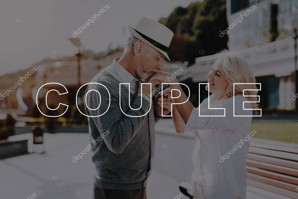 Kisses Hand. Bubbly Relationships. Walk. Love Story. Holding Hands. Beautiful Square. Sun. Elderly Man. Old Couple. Two Pensioners. Woman. Retired. Happy Together. Leisure Time. Have Fun.