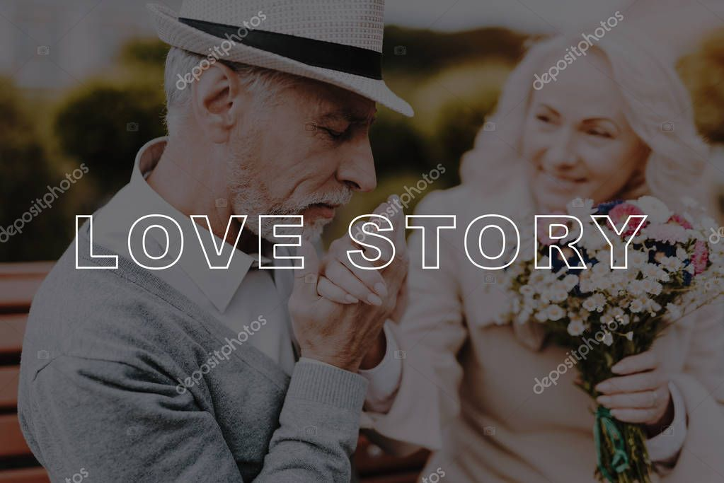 Kisses Hand. Flowers. Two Pensioners. Alley in Park. Bubbly Relationships. Love Story. Old Couple. Sit. Bench. Elderly Man. Woman. Gift. Retired. Happy Together. Leisure Time. Have Fun. Smiling.