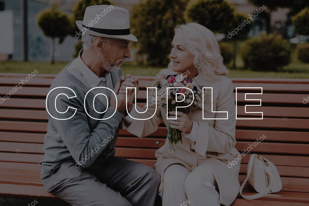 Old Couple. Kisses Hand. Flowers. Two Pensioners. Alley in Park. Bubbly Relationships. Love Story. Sit. Bench. Elderly Man. Woman. Gift. Retired. Happy Together. Leisure Time. Have Fun. Smiling.