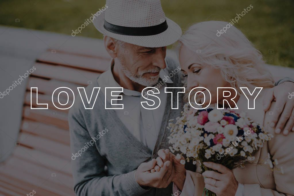 Happy Together. Two Pensioners. Hugs. Flowers. Bubbly Relationships. Alley in Park. Love Story. Old Couple. Gently Embraces. Sit. Elderly Man. Woman. Gift. Retired. Leisure Time. Have Fun. Smiling.