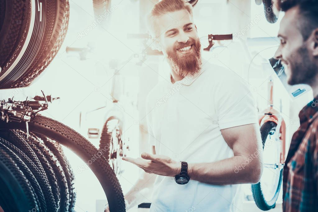Seller Helps Young Buyer Choose Tires for Bicycle in Sport Bike Store. Happy Bearded Professional Consultant Wearing White T-Shirt Shows Smiling Client Different Types of Goods.