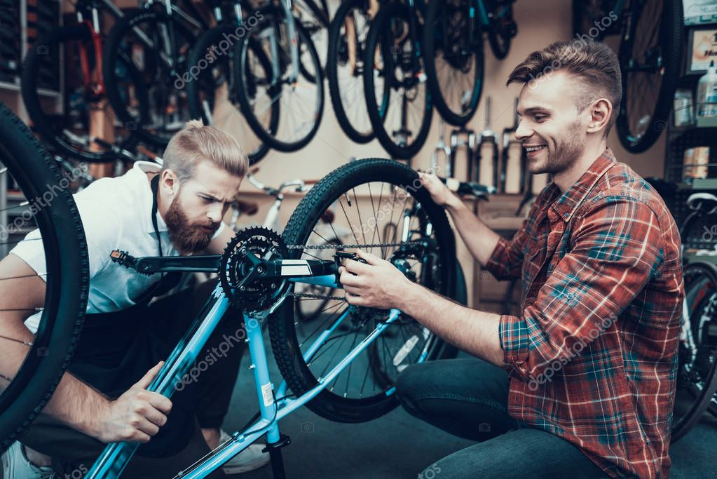 Two Guys Examine Bicycle in Sport Workshop. In Cycle Store Young Smiling Man Assisted Professional Repairman in Modern Bike Fixing. Bike Maintenance and Sport Shop Concept