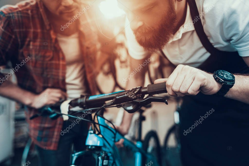 Guy and Repairman Fixes Bicycle in Sport Store. Portrait of Young Caucasian Man Wearing Apron Looks at Brake on Handlebar Examines and Fixes Modern Cycle. Bike Maintenance and Sport Shop Concept