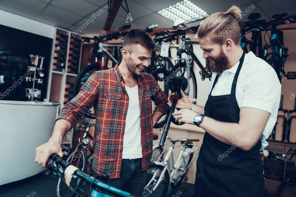 Guy and Repairman Fixes Bicycle in Sport Store. Portrait of Young Caucasian Man Wearing Apron Holds Saddle Examines and Fixes Modern Cycle. Bike Maintenance and Sport Shop Concept