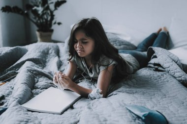 Little Girl Listens Music and Draws in Bedroom. Frowning Black-Haired Child Wearing Casual Clothes Uses White Earphones Lying on Large Gray Bed with Notepad. Leisure Time Concept