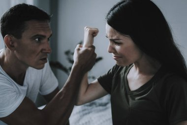 Fight and Quarrel between Woman and Man at Home. Portrait of Married Couple Sitting on Gray Bed and Arguing. Angry Husband Hold Wifes Hand Conflict in Bedroom. Family Violence Concept