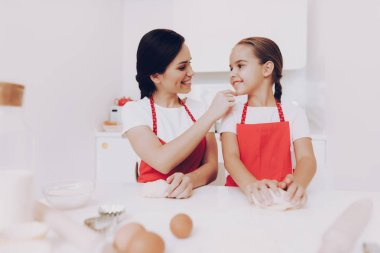 Mom Praises Little Girl for a Good Work in the Kitchen. Cooking For Family. Happy Time. Aproan for Good Girl and Young Mom. Preparation for Young Mom. Girl and Mom Happy Time. Kitchen and Happy Women.