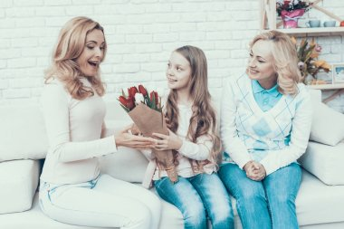 Girl Presenting Bouquet of Tulips to Smiling Mother. Mother with Daughter. Smiling Women. Celebration Concept. Happy Family. Sitting at Home. Red Flower. White Flower. Holiday in March. Mother's Day.