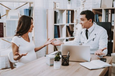 Pregnant Girl at the Gynecologist Doctor. Doctor is a Young Man. People Sitting at Table. Persons is Talking and Gesticulating. Upset Woman is Crying. Man is Smiling. People Located at Clinic.