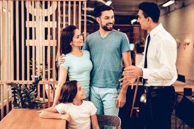Young Family Consulting With Furniture Seller. Happy Together. Bright Office. Sunny Day. Presentation On A Laptop. Business Meeting. Room Interior. Parents And Daughter. Look Around The Store.